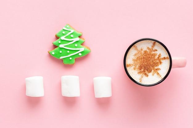 Café de natal com biscoito e marshmallow em fundo rosa, layout plano. pão de mel em forma de árvore de abeto e café com leite decorado com floco de neve.