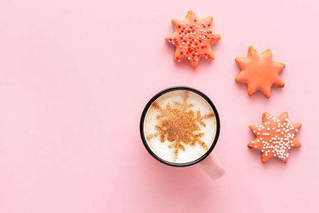 Café de natal com biscoitos em forma de estrela em fundo rosa pastel, vista superior. pão de mel com glacê festivo e cappuccino decorado com floco de neve de canela.