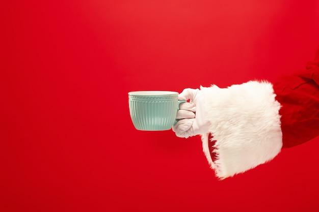 Café de natal. mão de santa segurando a xícara de café isolada em um fundo vermelho com espaço para texto.