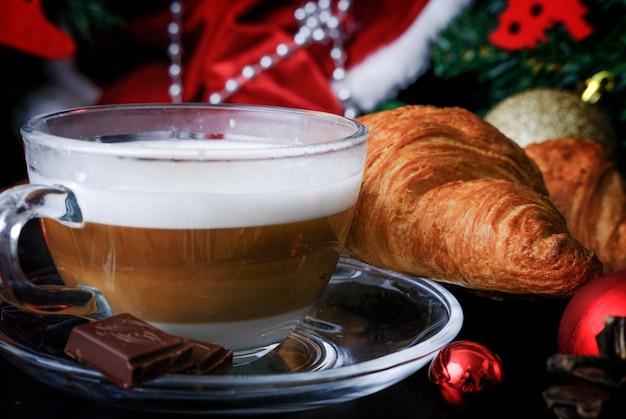 Café de natal. xícara de cappuccino quente com camadas visíveis e croissants e decoração de natal