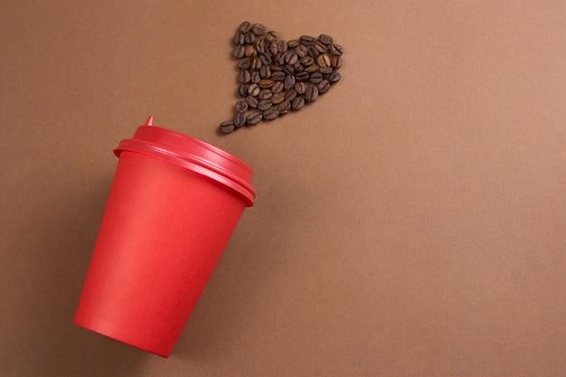 Café de papel para ir o copo e o coração feito de grãos de café