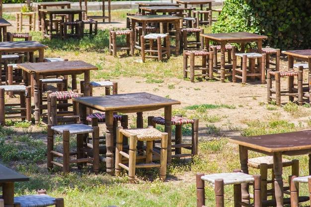 Café de rua de verão com mesas e cadeiras de madeira