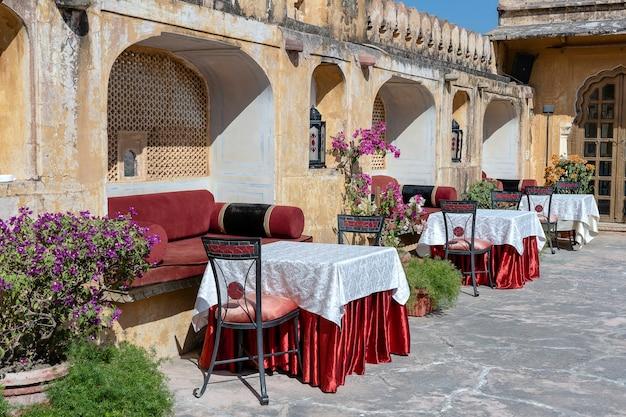 Café de rua na cidade velha, do lado de fora em jaipur, rajasthan, índia. mesa, sofá e cadeiras perto da parede velha