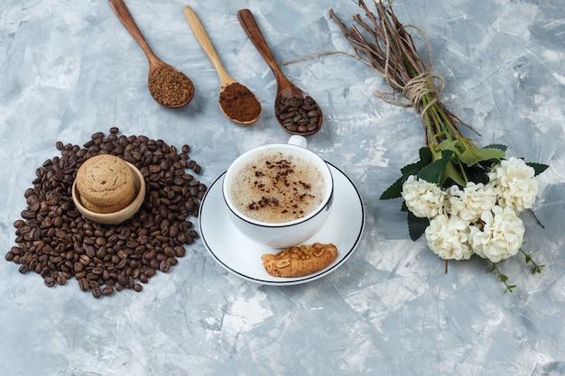 Café de vista de alto ângulo na xícara com biscoitos, grãos de café, café moído, flores sobre fundo cinza sujo. horizontal