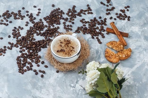 Café de vista de alto ângulo na xícara com biscoitos, grãos de café, flores, paus de canela em fundo de gesso cinza. horizontal