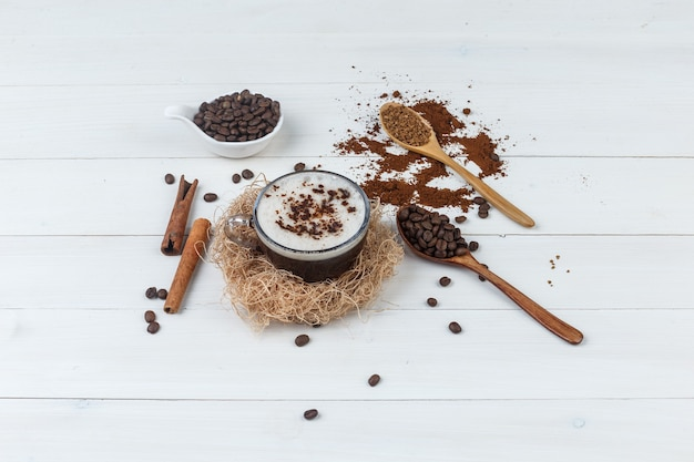 Café de vista de alto ângulo na xícara com café moído, grãos de café, paus de canela em fundo de madeira. horizontal