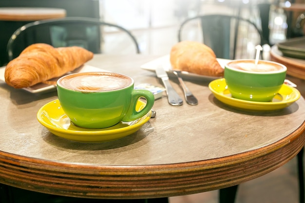 Café delicioso com croissan na mesa de madeira rústica no café.