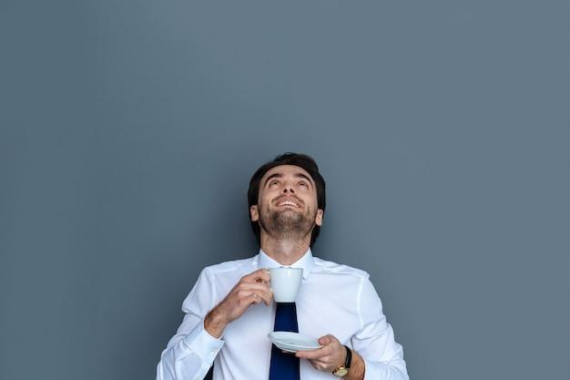 Café delicioso. homem feliz, positivo e encantado, olhando para cima e sorrindo enquanto saboreia sua bebida