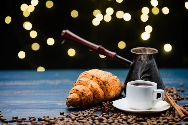 Café derrama em uma xícara sobre uma mesa de madeira azul com grãos de café e um croissant