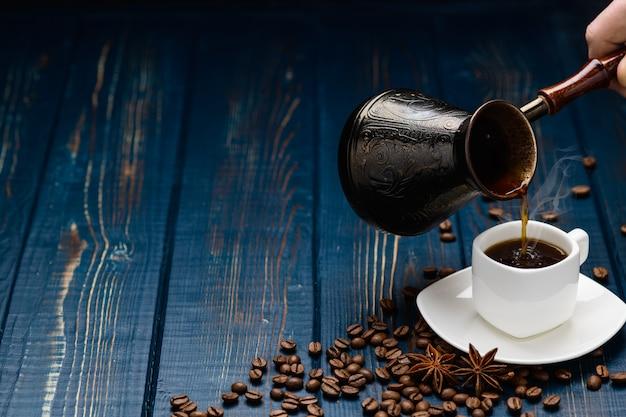 Café derrama em uma xícara sobre uma mesa de madeira azul com grãos de café