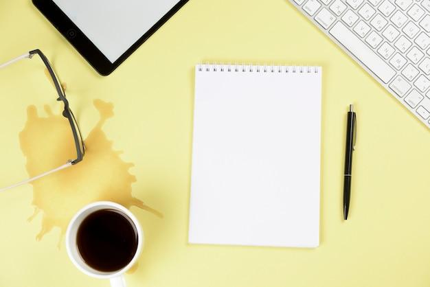 Café derramado; óculos; tablet digital; teclado; bloco de notas e caneta espiral em branco sobre fundo amarelo