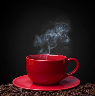 Café do copo vermelho closeup e feijão de café fresco