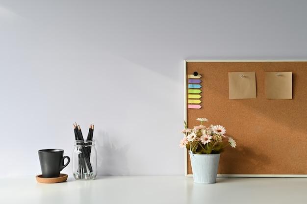 Café do espaço de trabalho, lápis, flor e nota pegajosa a bordo com mesa de escritório e luz da manhã.
