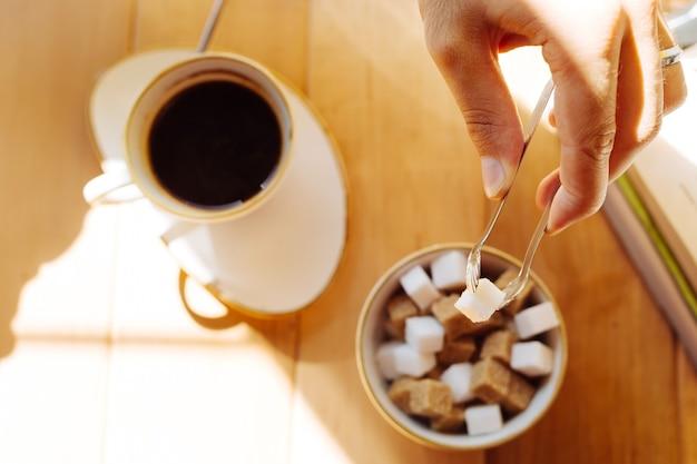 Café doce. vista superior de um pedaço de açúcar em pinças de açúcar ao ser colocado em um café