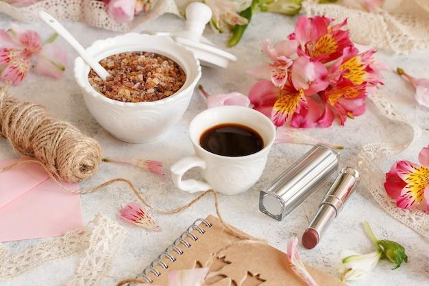 Café e açúcar em uma mesa branca entre flores cor de rosa close-up