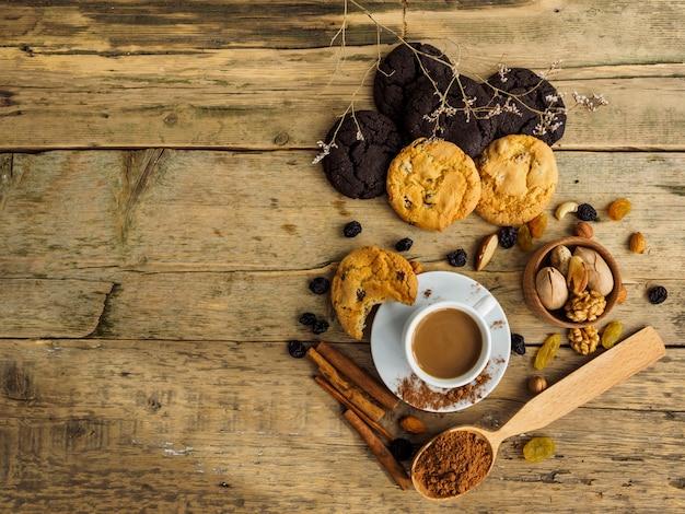 Café e biscoitos em uma mesa de madeira. espaço para texto na mesa.