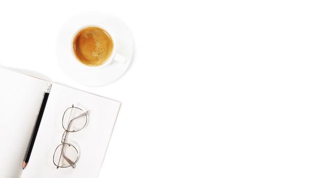 Café e bloco de notas com óculos em um fundo branco. copyspace