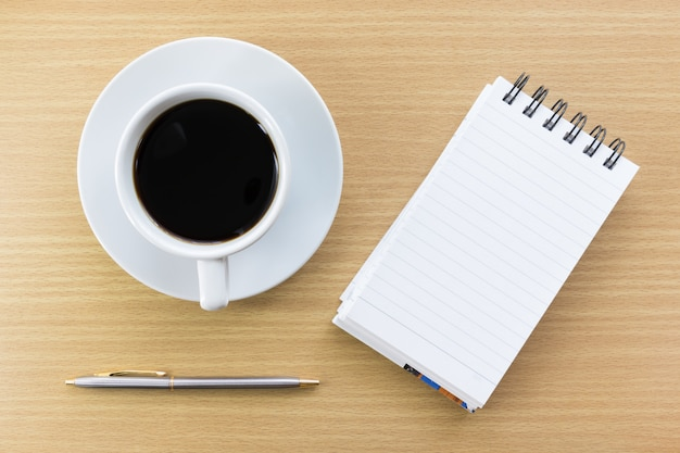 Café e bloco de notas na mesa de madeira