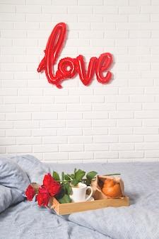 Café e bolos em uma bandeja de madeira. com um buquê de flores na cama.