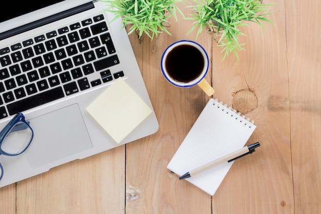 Café e caderno aberto perto do laptop