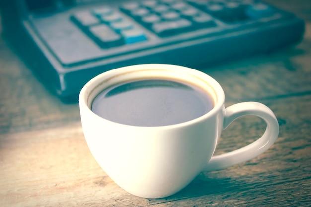 Café e calculadora na mesa de madeira