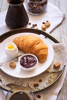 Café e croissant, ovos e geléia no café da manhã