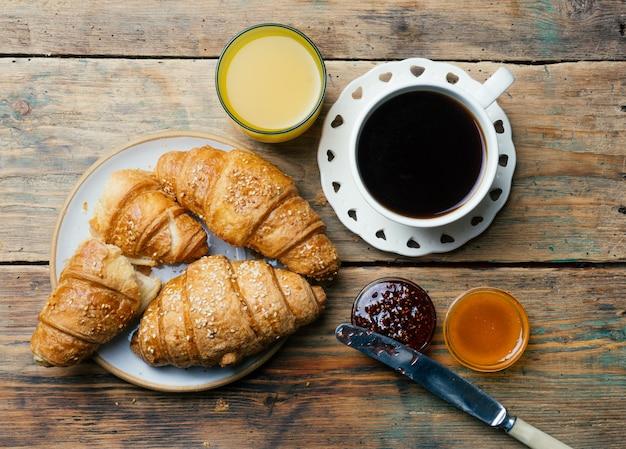 Café e croissants com geléia e suco de laranja. café da manhã típico francês (petit déjeuner)