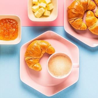 Café e croissants em um fundo brilhante e moderno, vista de cima