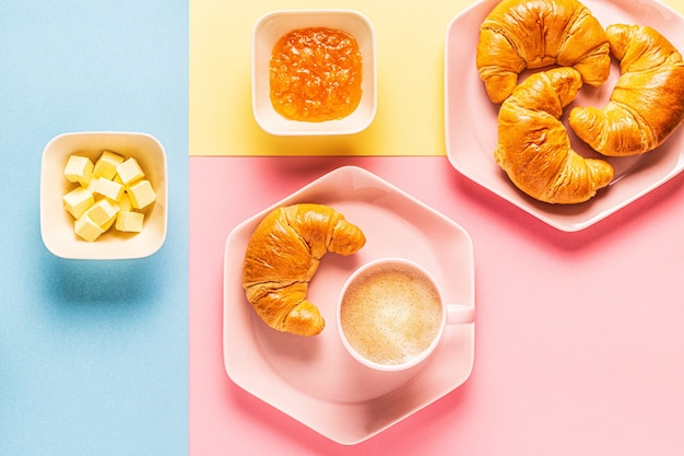 Café e croissants em um fundo brilhante e moderno, vista superior, plana leigos.