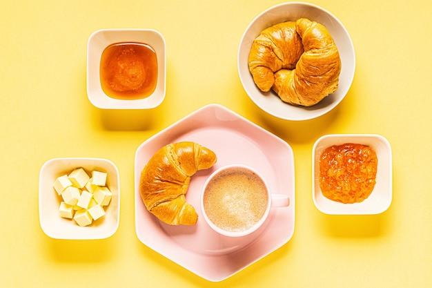 Café e croissants no café da manhã em um fundo amarelo, vista de cima,