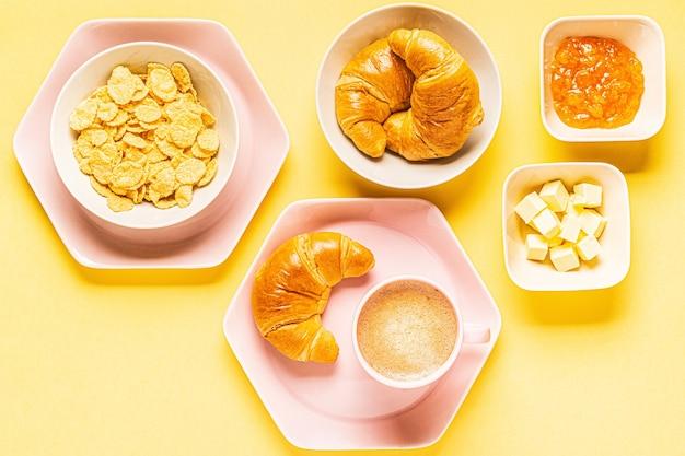 Café e croissants no café da manhã em um fundo amarelo, vista superior, plana leiga.