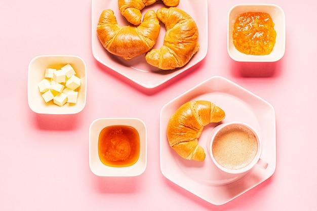 Café e croissants no café da manhã em um fundo rosa, vista de cima,