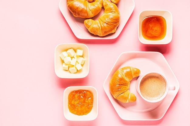 Café e croissants no café da manhã em um fundo rosa