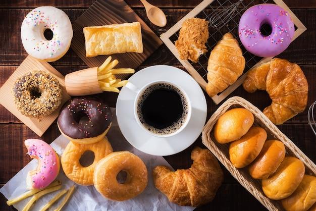 Café e diversos tipos de junk food na mesa de madeira da vista superior.