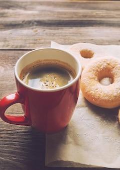 Café e donuts polvilhados com açúcar de confeiteiro na superfície de madeira rústica. imagens retrô em tons.