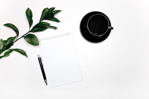 Café e flores em fundo branco.