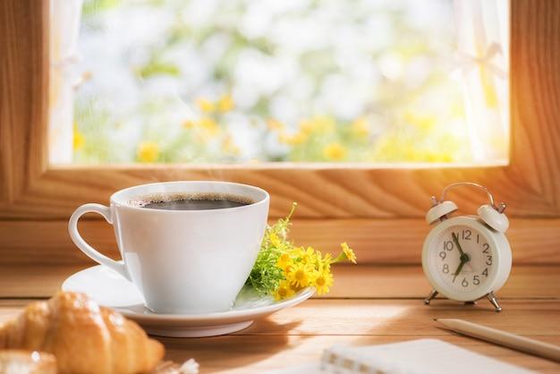 Café e flores para o café da manhã colocados perto da janela com o sol da manhã