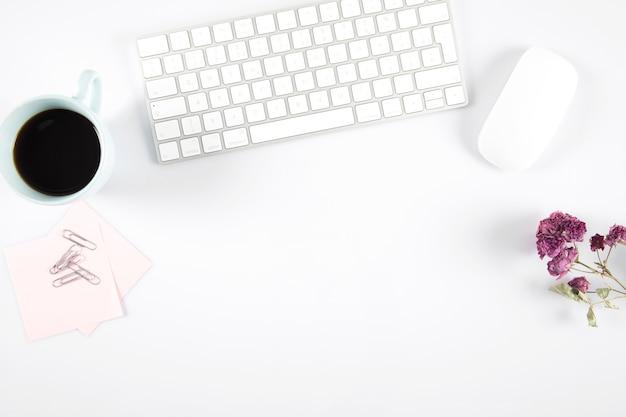 Café e flores perto de mouse e teclado de computador