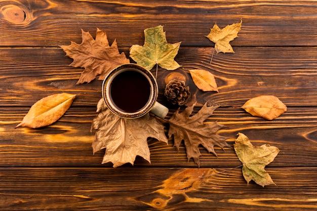 Café e folhas no fundo de madeira