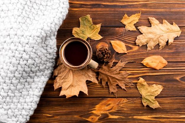 Café e folhas secas no fundo de madeira
