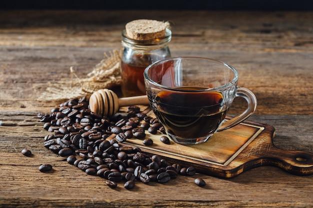 Café e grãos de café com mel na mesa de madeira