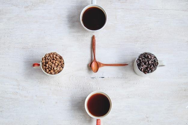 Café e grãos de café contra o fundo branco, formando o conceito de relógio