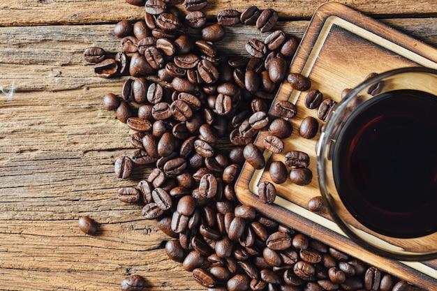 Café e grãos de café na mesa de madeira