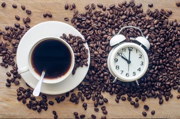 Café e grãos de café são colocados perto do despertador