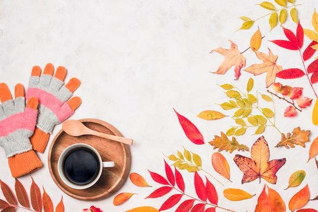 Café e luvas com folhas de outono copiam o espaço
