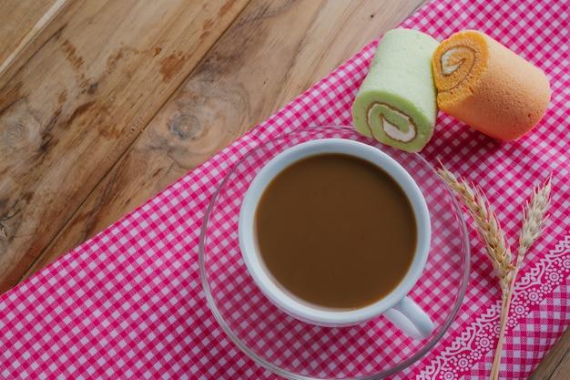 Café e pão colocados em um pano estampado rosa sobre um piso de madeira marrom.