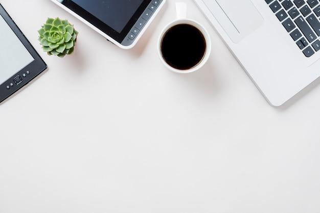 Café e planta perto de laptop e e-books