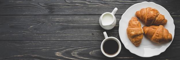 Café e produtos lácteos perto de prato com croissants
