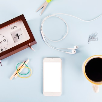 Café e smartphone perto de artigos de papelaria e relógio
