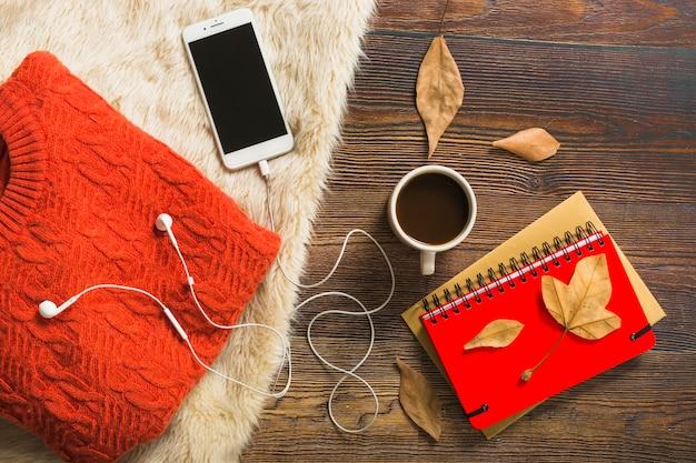 Café e smartphone perto de jumper e notebooks